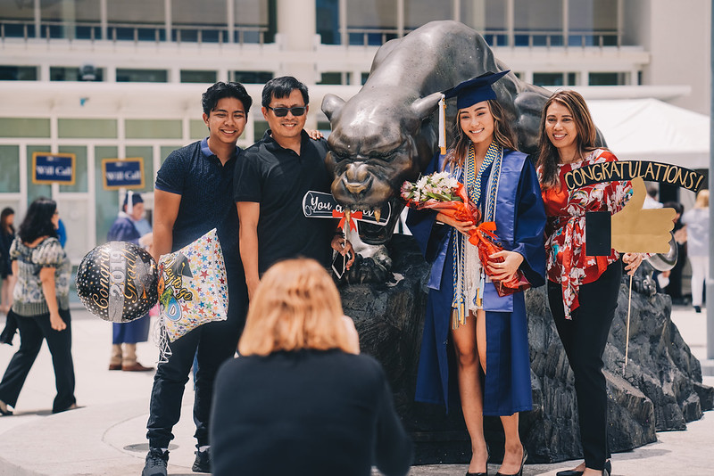 Photo of female grad in front of Panther statue with family