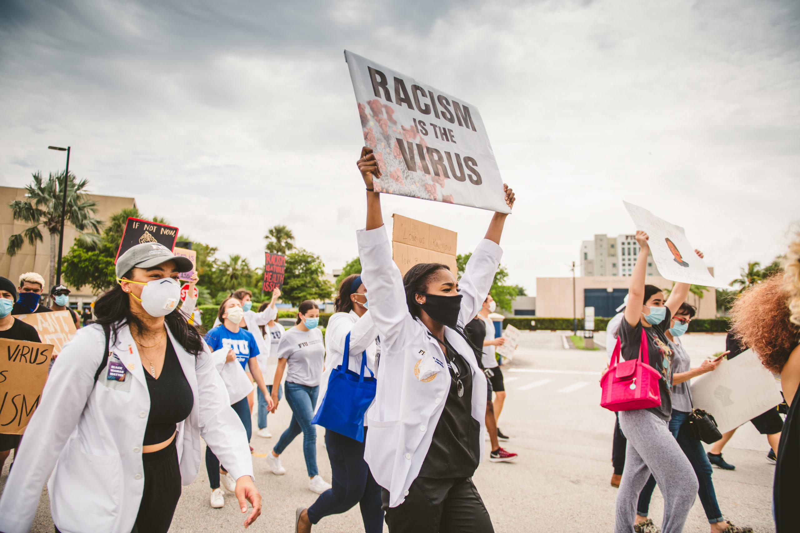 Photo of individuals holding a sign that says Racism is the Virus at a march